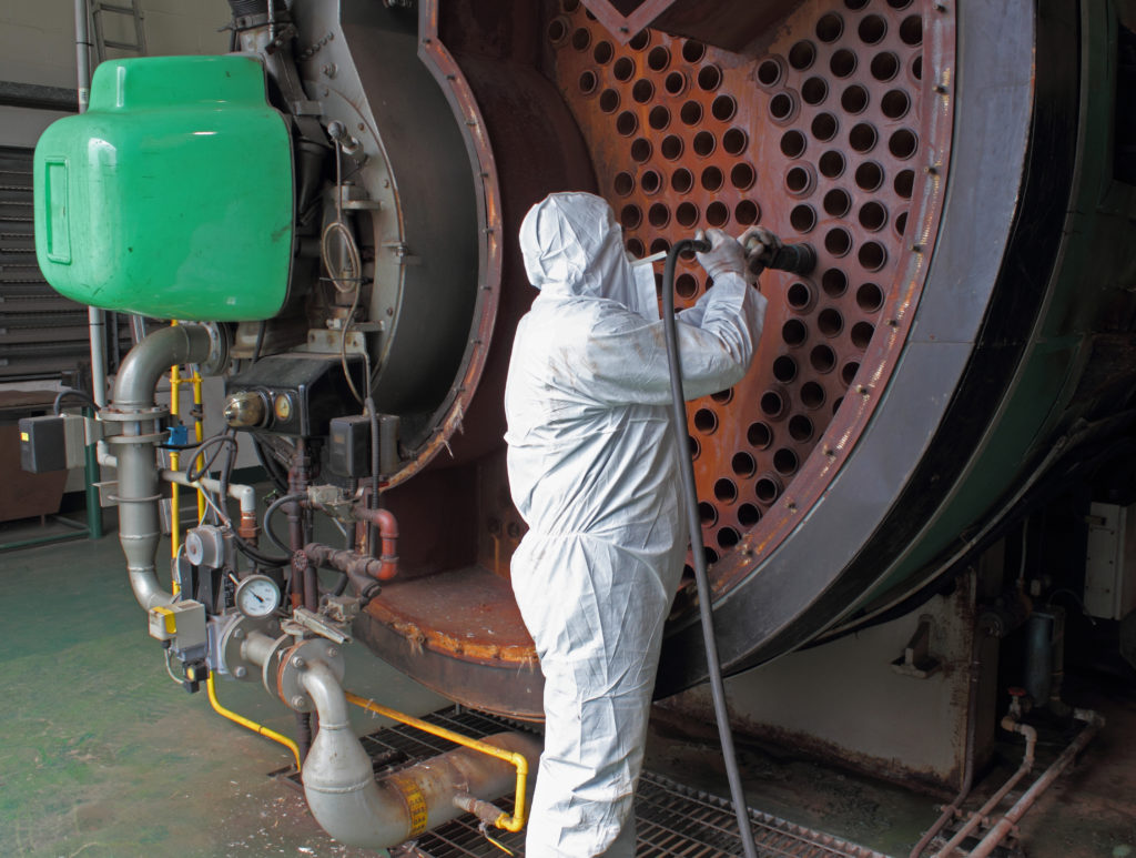 a man cleaning a large industrial machine